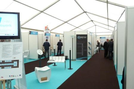 Salon professionnel avec exposants et stands modulaires de diffe´rentes dimensions en me´lamine´, avec moquette.